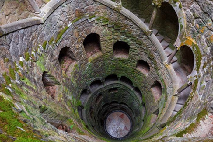 """Der spiralartig in die Tiefe führende Steinturm, der """"Initationsbrunnen"""" in der Gartenanlage der Quinta da Regaleira. Hierher führen nur unterirdische Gänge bzw. ein im Fels versteckter Eingang."""